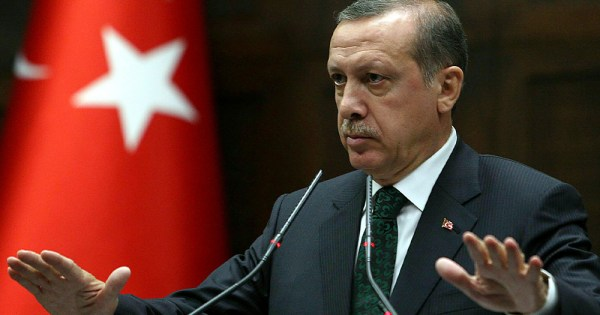 The President of Turkey, a stern man in a suit, speaks from a podium