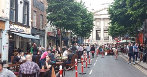 People sitting at tables on a city street