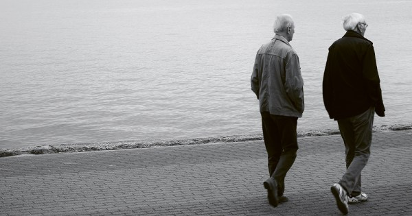 Two old men walking alongside a dock