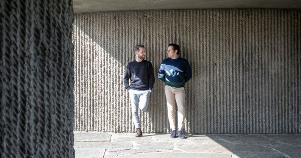 Two men leaning against a wall