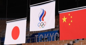 Three flags hang from the rafters of a building