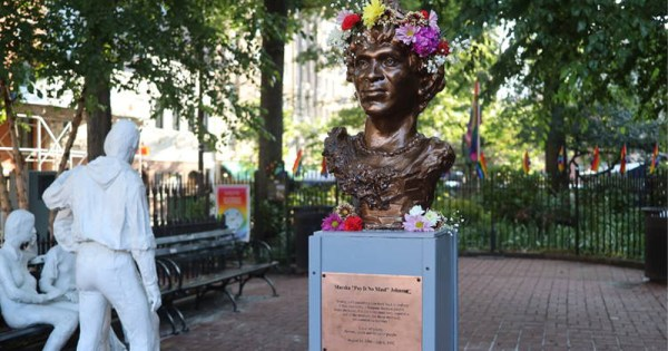 The statue of Marsha P Johnson is shown with flowers in her hair. George Segal's 'Gay Liberation' monument is seen to the left.