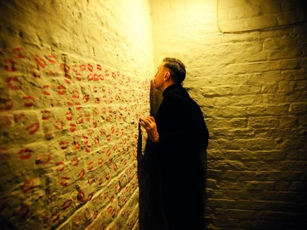 Image of Francis Fay kissing a wall in Kilmainham Gaol