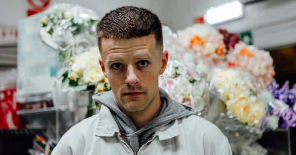 A man surrounded by bouquets of flowers in plastic looks into the camera