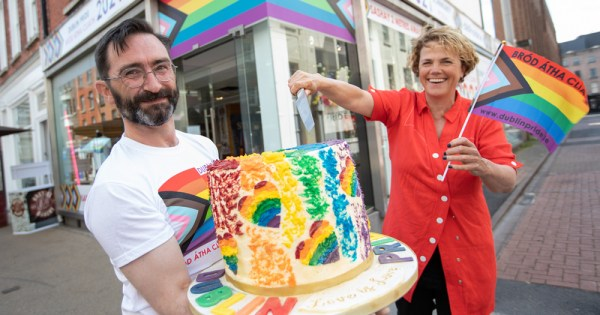 Bearded man holding a colourful cake with women dressed in red holding a knife above the cake while waving a miniature Pride flag. They are standing in front of a shop marked with Pride flag.