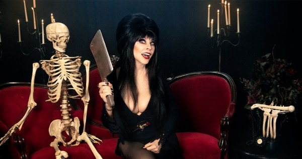 Elvira releases her special with a publicity photo featuring a gothic woman holding a cleaver sitting on a couch beside a skeleton
