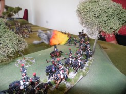 French Chasseurs advance through the wood on the hill while their artillery fires on the town.