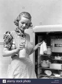 1930s-woman-wearing-a-white-apron-taking-milk-out-of-the-refrigerator-AAM1RN