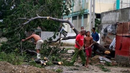 Varias personas trabajan talando árboles derribados por el paso del huracán Sandy por el poblado de Caimanera, en la provincia de Guantánamo (Cuba).