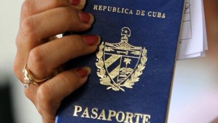 Una mujer muestra dos pasaportes cubanos en una oficina regional de la Dirección de Inmigración y Extranjería en La Habana (Cuba).