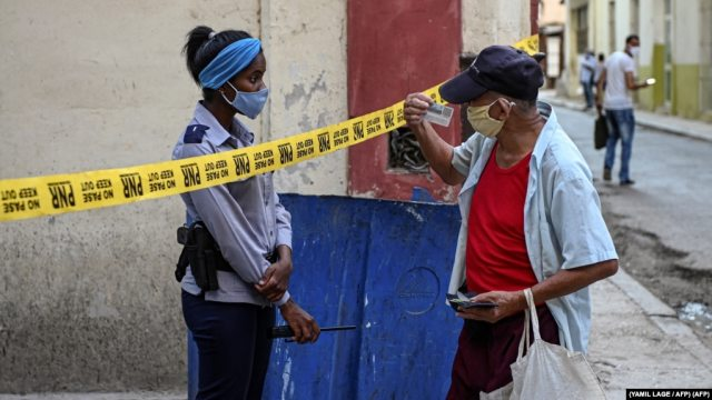 Una oficial de policía exige identificación a un ciudadano en una calle de La Habana cerrada por coronavirus. (YAMIL LAGE / AFP)