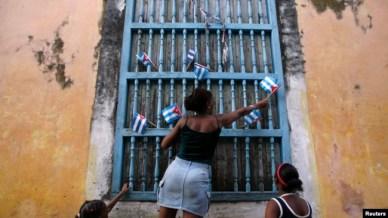 Una mujer adorna una ventana con banderas de papel en La Habana, Cuba, 2007. Reuters.