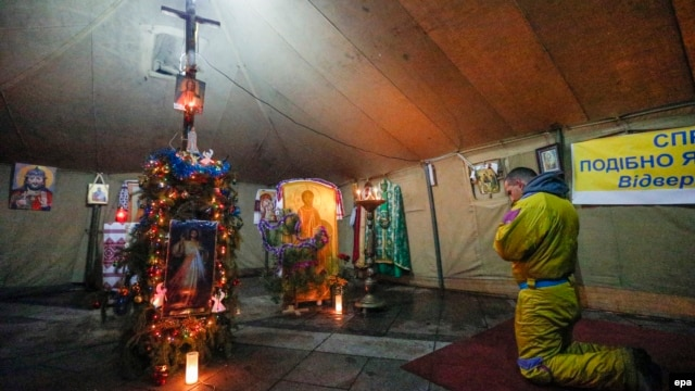 Protesters pray in a tent-chapel on Independence Square, Kyiv, January 6, 2014