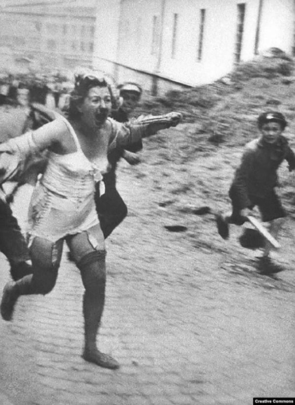 Жінка єврейської національності втікає від юрби у Львові, місті, що в міжвоєнний час було польським, потім окуповане СРСР і врешті нацистами, фото червня чи липня 1941 року. За активного заохочення нацистів євреї радянської України й інших окупованих територій зазнавали справжніх жахіть. Тисячі їх були замучені і вбиті в перебігу погромів, влаштованих у Центральній і Східній Європі