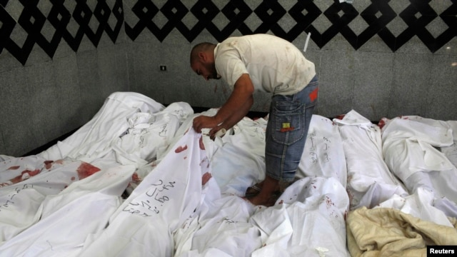 A man searches for bodies of his relatives who were supporters of ousted Egyptian President Muhammad Morsi after scores were killed in Cairo.