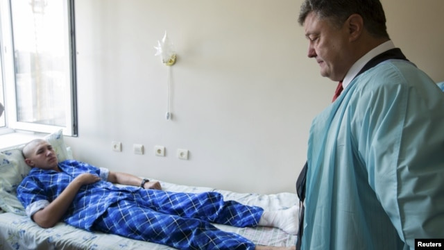 Ukrainian President Petro Poroshenko visits a serviceman who was wounded during the August 31 protest outside parliament. Three National Guardsmen were killed in the violence.