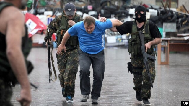 Members of the Vostok Battalion, a pro-Russia militia, escort an activist of the so-called People's Republic of Donetsk after detaining several of them following their storming of the regional state building in the eastern city of Donetsk on May 29.