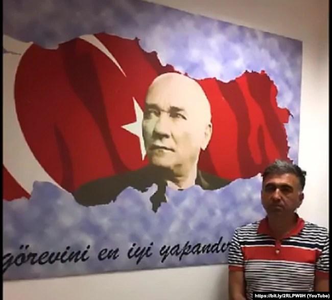 Стоп-кадр: Саліх Зекі Їгіт після депортації до Туреччини. На цьому кадрі не видно, що руки в нього зв'язані. Біля цього ж самого прапора покажуть і Юсуфа Інана