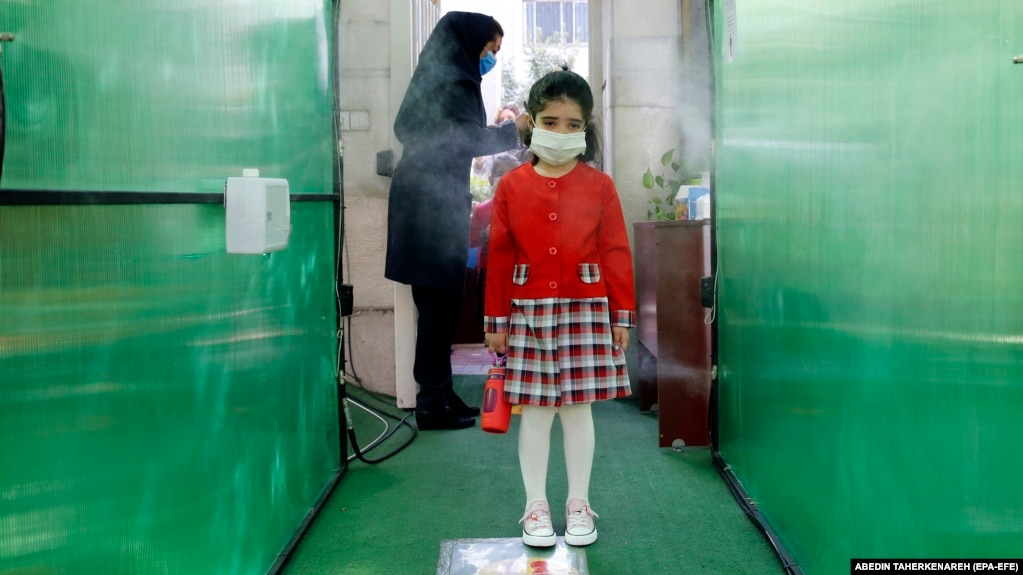 An Iranian elementary schoolgirl passes through a disinfection tunnel as she attends school in north Tehran.
