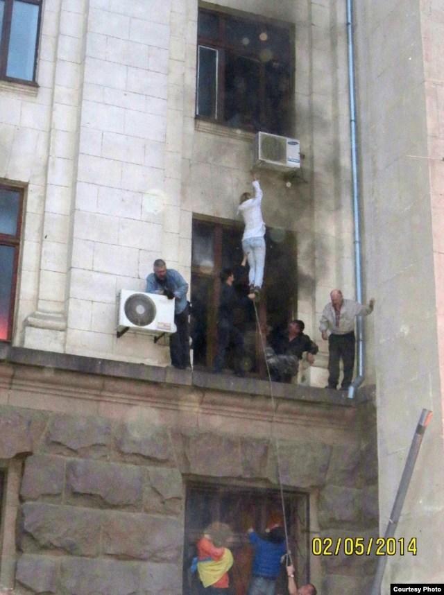 Проукраинские активисты помогают эвакуировать людей из горящего здания Дома профсоюзов. Одесса, 2 мая 2014 года