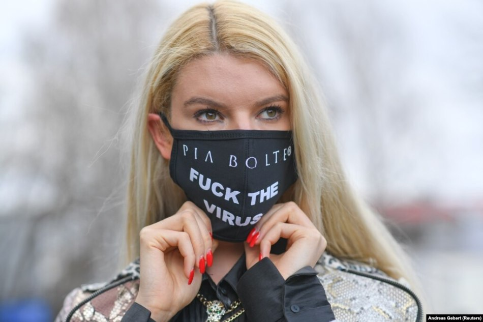 German fashion model Franziska wears a mask with a message that was tailored at the Pia Bolte Style shop in Munich.