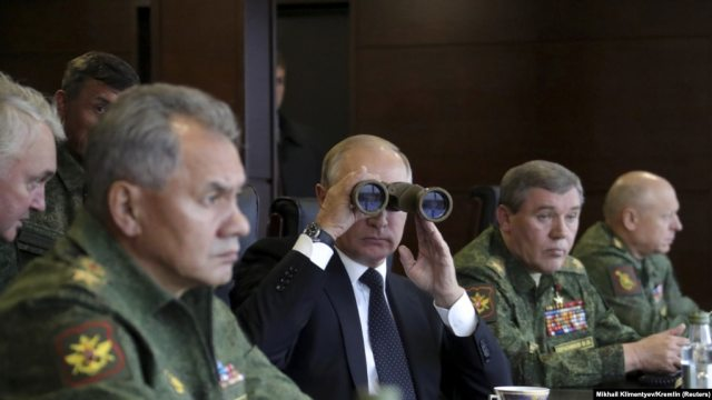 Russian President Vladimir Putin uses binoculars to watch the Zapad 2017 war games, held by Russian and Belarusian forces, with Defense Minister Sergei Shoigu (left).