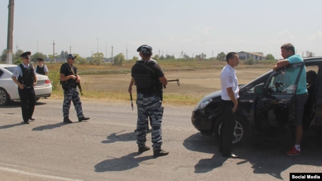 Crimean Tatar activists have reported armed checkpoints being erected at scattered sites around the peninsula.