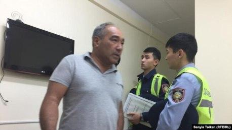 Один из бывших коллег Максата Досмагамбетова Сейсен Аспентаев (слева) и сотрудники полиции в больнице. Актау, 28 сентября 2018 года.