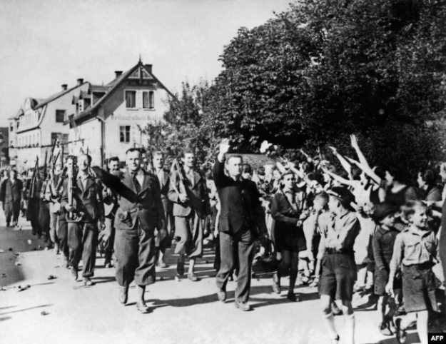 Люди приветствуют добровольцев, участвовавших в параде судетских немцев в Свободном корпусе 23 сентября 1938 года недалеко от Аша, Чехословакия, после аннексии немецко-нацистской армией Судетской области Чехословакии