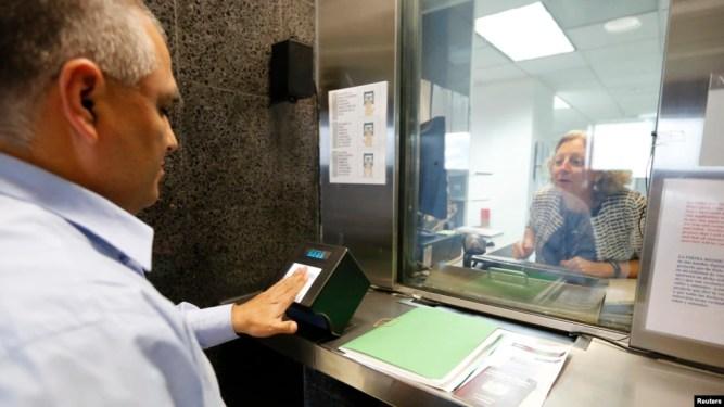 Một viên chức lãnh sự Hoa Kỳ đang lấy vân tay của một đơn đương xin thị thực ở Lima, Peru.