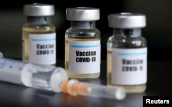 "Ampul-ampul dengan stiker ""Vaksin Covid-19"" dan alat suntik, 10 April 2020. (Foto: Ilustrasi/Reuters)"