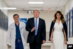 President Donald Trump, accompanied by first lady Melania Trump and Dr. Igor Nichiporenko, speaks to reporters while visiting with medical staff at Broward Health North in Pompano Beach, Fla., Feb. 16, 2018.