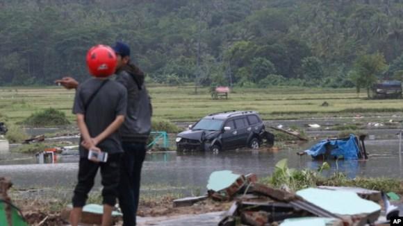 Afectados de pie cerca a un coche destruído por un tsunami en Carita, Indonesia, el 23 de diciembre del 2018