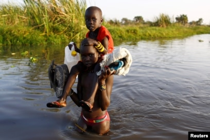 FILE - Children cross a body of water to reach a registration area prior to a food distribution carried out by the United Nations World Food Program (WFP) in Thonyor, Leer state, South Sudan.