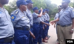 Acting police chief Matanga inspecting some policemen and police woman.