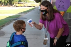 In a photo provided by Newton County Schools, teaching assistant Crystal May talks to kindergarten student Lewis Henry Thompson, 5, as she takes his temperature at Newton County Elementary School in Decatur, Mississippi, Monday, Aug. 3, 2020.