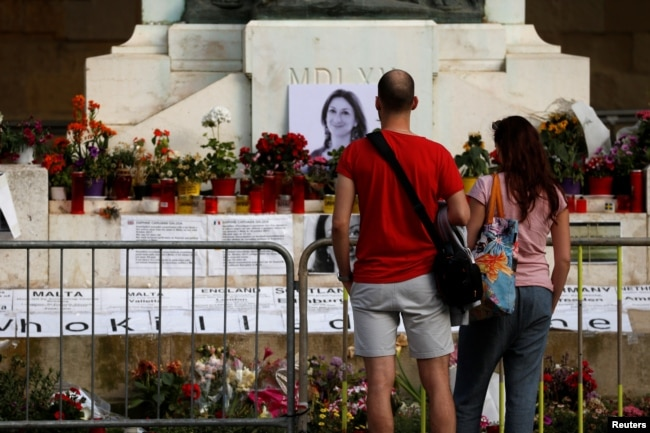 FILE - People look at the makeshift memorial to assassinated anti-corruption journalist Daphne Caruana Galizia on the Great Siege Monument after the police blocked off access to it, in Valletta, Malta, April 22, 2018.