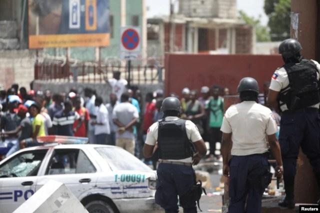 La Policía Nacional de Haití vigila una zona comercial que fue saqueada durante las protestas contra los aumentos de los precios del combustible en Puerto Príncipe, Haití, el 8 de julio de 2018. REUTERS / Andres Martinez Casares.