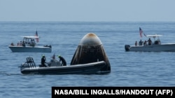 Esta foto del folleto publicada por cortesía de la NASA muestra equipos de apoyo y navegantes recreativos curiosos que se acercan a la nave espacial SpaceX Crew Dragon Endeavour poco después de su aterrizaje.  (NASA)