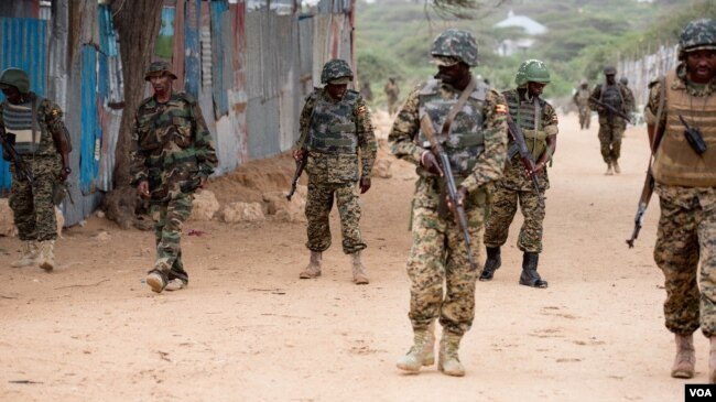FILE - AMISOM soldiers and armored vehicles pass a woman riding a cart during a patrol at a village outside Mogadishu, Sept. 19, 2016. (Photo: J. Patinkin/VOA)