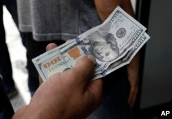 A Turkish man waits to change his U.S. dollars with Turkish liras inside a currency exchange shop in Ankara, Aug. 10, 2018. A financial shockwave ripped through Turkey on Friday as its currency nosedived on concerns about its economic policies and a dispute with the U.S., which President Donald Trump stoked further with a promise to double tariffs on the NATO ally.