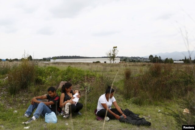 FILE - A group of Central American immigrants sit between vegetation for fear of organized crime bands in Huehuetoca, near Mexico City, June 1, 2015. An increasing number of Central Americans are sneaking across Mexico's border en route to the United States.
