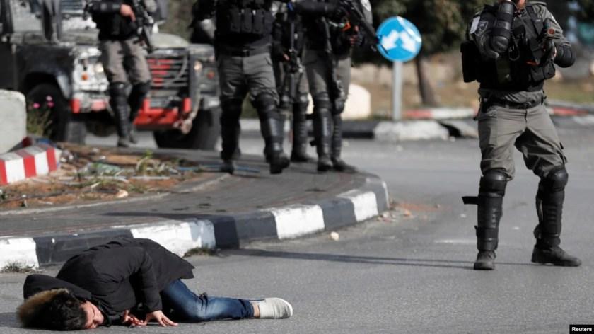 Một người đàn ông Palestine nằm trên mặt đất sau khi bị cảnh sát biên phòng Israel bắn gần khu định ngư Do Thái Beit El, gần thành phố Ramallah ở Bờ Tây,ngày 15 tháng 12, 2017.