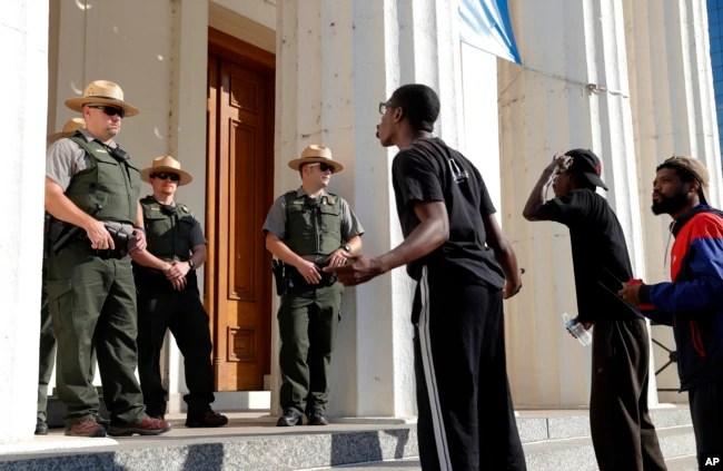 Manifestantes gritan a oficiales de policía mientras marchan por el centro de la ciudad después que una corte absolvió de culpa a un policía acusado de matar a un hombre negro en 2011. Sept.15, 2017.