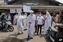 Pejabat pemerintah berpakaian pocong untuk mewakili para korban Covid-19 di sebuah pasar di Tangerang, 16 September 2020. (Foto : AP)