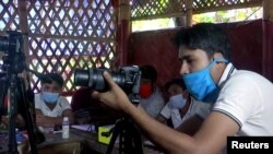 Seorang instruktur memberikan pelatihan fotografi di kamp pengungsi Rohingya di Bangladesh (foto: Reuters).