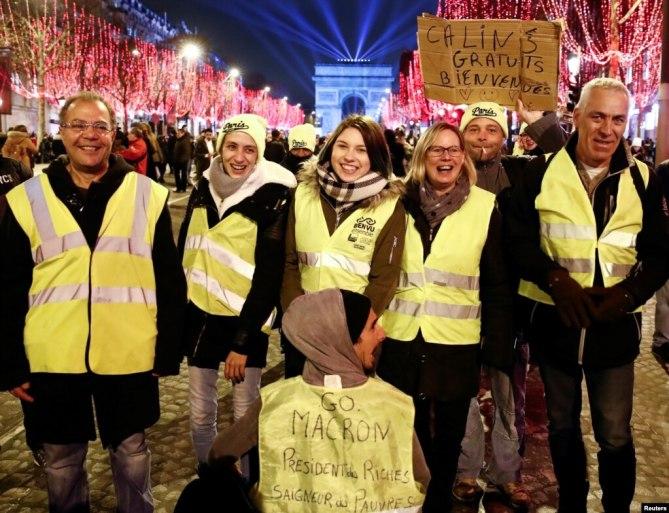 """Một số người dân Pháp mặc những chiếc gilê vàng tham gia buổi lễ đón mừng năm mới gần Arc de Triomphe, Paris, 31/12/2019. Một trong những đoạn khẩu hiệu trên áo gile ghi :""""Cút đi Macron, tên Tổng thống của người giàu, kẻ hạ sát dân nghèo,""""."""