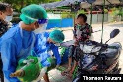 میانمار میں کرونا وائرس کے ایک مریض کی سانس بحال کرنے کے لیے طبی عملہ اسے آکسیجن دے رہا ہے۔