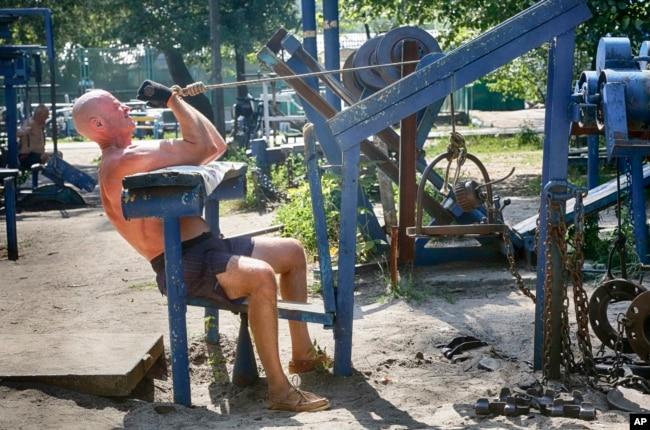 A man lifts weights at an outdoor gym in a city park in Kiev, Ukraine. (AP Photo)