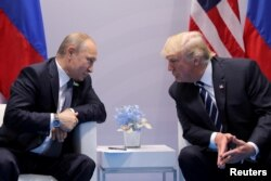 FILE - Russia's President Vladimir Putin talks to U.S. President Donald Trump during their bilateral meeting at the G20 summit in Hamburg, Germany, July 7, 2017.